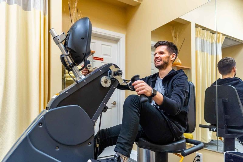 A man rides an exercise bike at Advance Physiotherapy Clinic