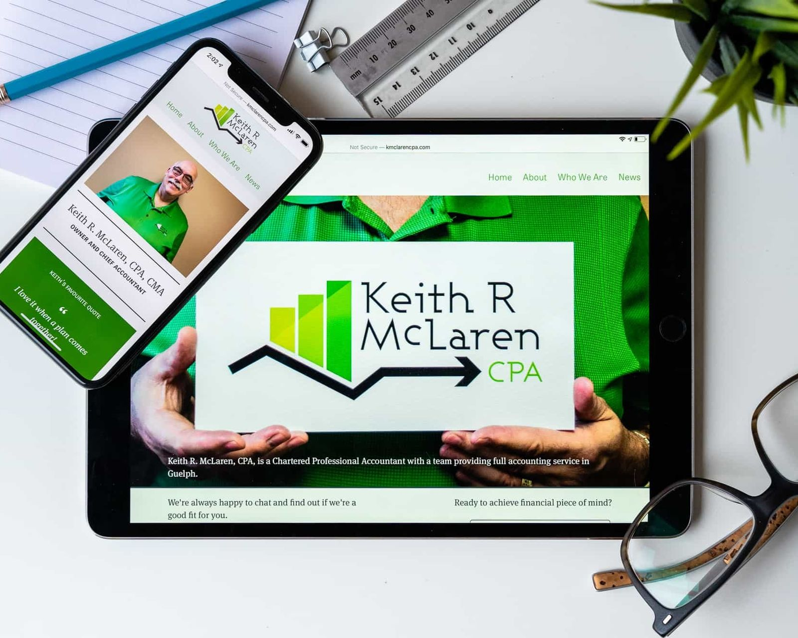 The Keith McLaren website on a tablet and a smartphone with glasses and other desk apparel nearby